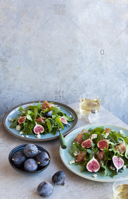 Two plates of green leaf salad with figs and ham
