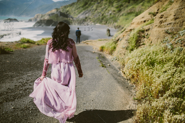 Bride in pink wedding dress walking to the beach.