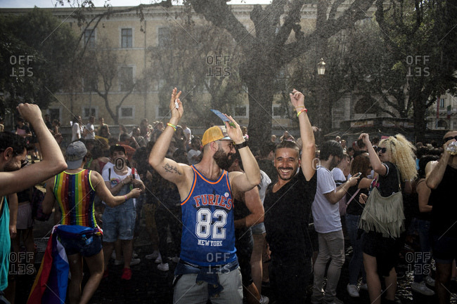 Rome, Italy - June 10, 2017: Two men with arms raised standing among crowd at gay pride celebration