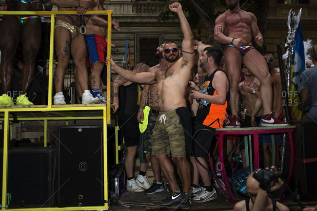 Rome, Italy - June 10, 2017: Bare chested man with arm raised standing among crowd at gay pride celebration