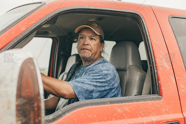 Native American man driving red truck