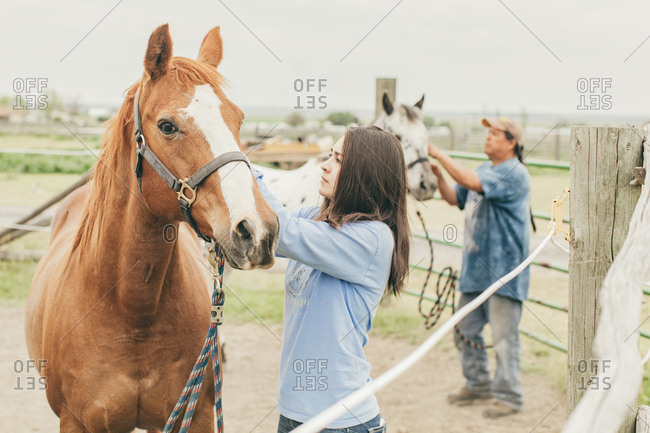 Native American father and daughter caring for their horses