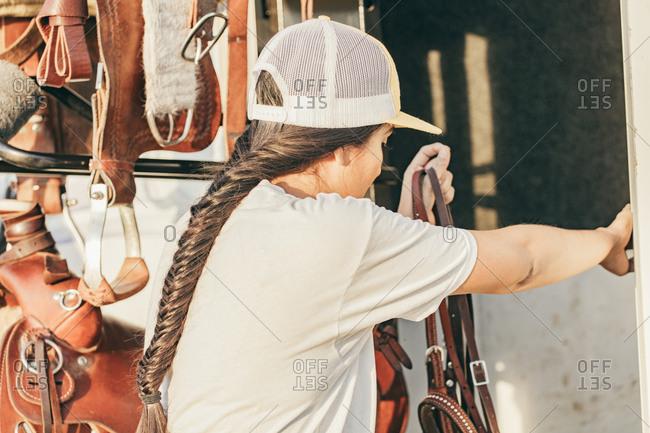 Native American girl preparing gear to ride horses