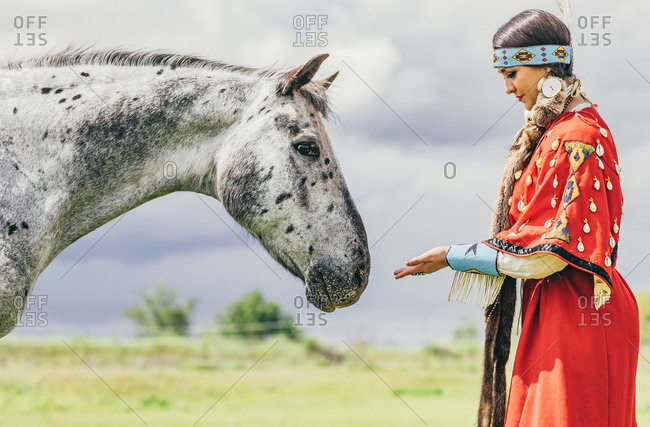 Girl dressed in Native American regalia with a white spotted horse