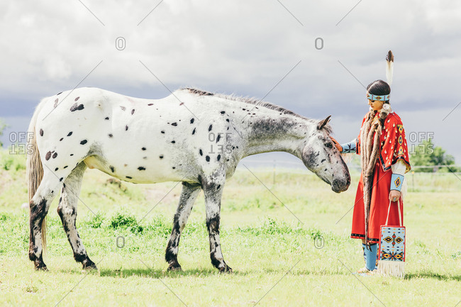 Young woman dressed in Native American regalia petting a white spotted horse
