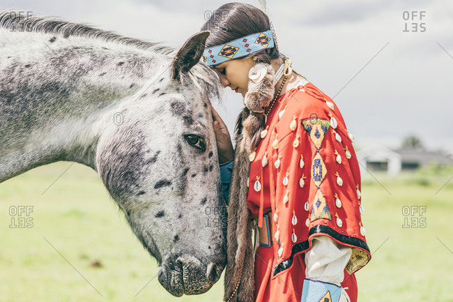 Girl dressed in Native American regalia touching a white spotted horse
