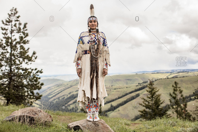 Young woman in Native American regalia standing on rock