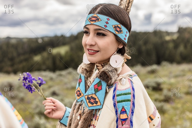 Girl holding purple flowers while wearing in Native American regalia