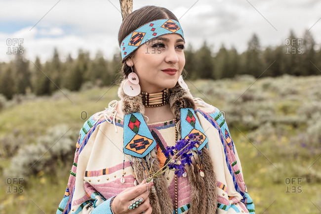 Girl wearing in Native American regalia looking away