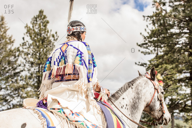 Girl dressed in Native American regalia riding a white spotted horse