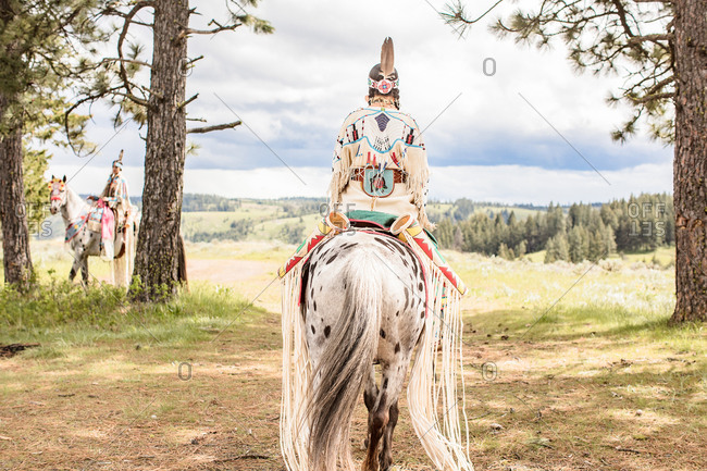 Rear view of girl dressed in Native American regalia riding a white spotted horse