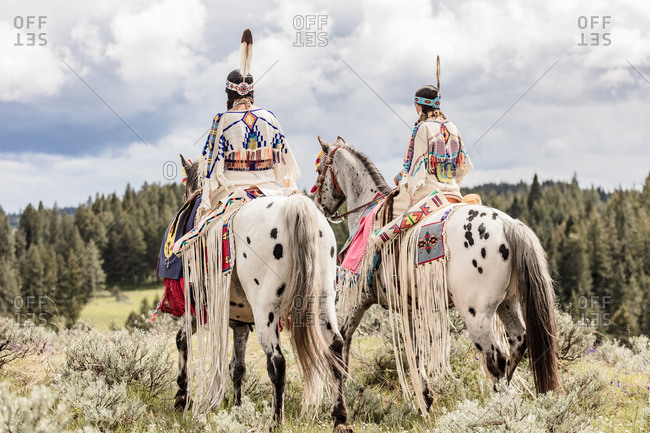 Sisters dressed in Native American regalia riding white spotted horses