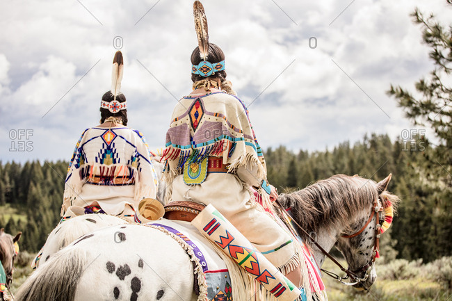 Rear view of sisters dressed in Native American regalia riding white spotted horses