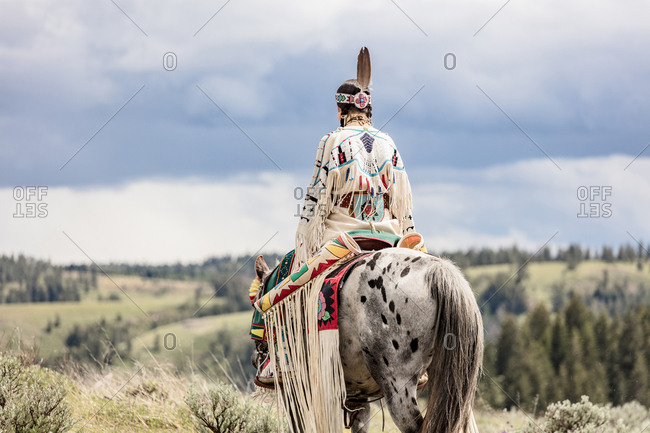 Rear view of young woman dressed in Native American regalia riding a white spotted horse