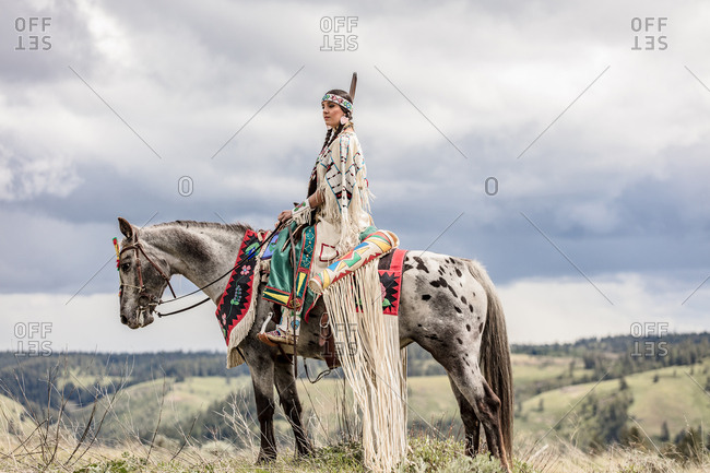 Side view of young woman dressed in Native American regalia riding a white spotted horse