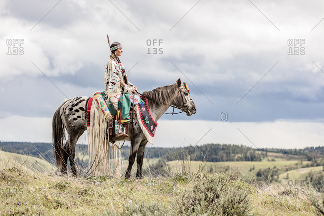 Side view of girl dressed in Native American regalia riding a white spotted horse