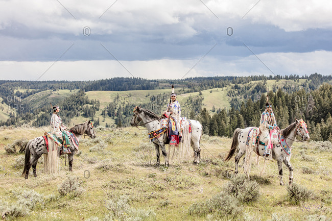 Three Native American sisters dressed in regalia riding horses