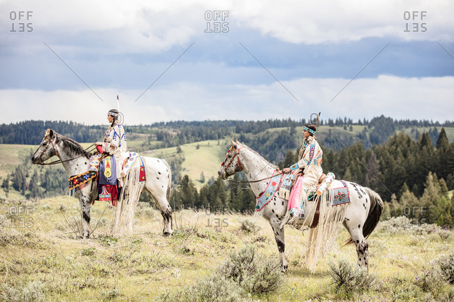 Two Native American sisters dressed in regalia riding horses