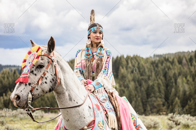 Native American young woman dressed in regalia riding a horse