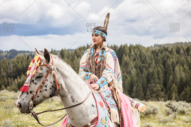 Native American girl dressed in regalia riding a horse