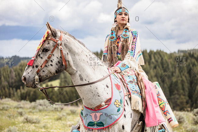 Native American young woman dressed in regalia riding a spotted horse