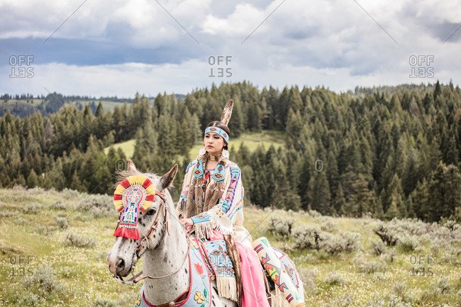 Native American girl dressed in regalia riding a spotted horse on the Umatilla Reservation, Pendleton, Oregon
