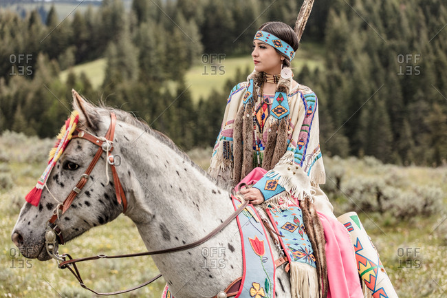Native American girl dressed in regalia riding a spotted horse