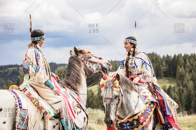 Two Native American sisters in regalia riding horses on the Umatilla Reservation, Pendleton, Oregon