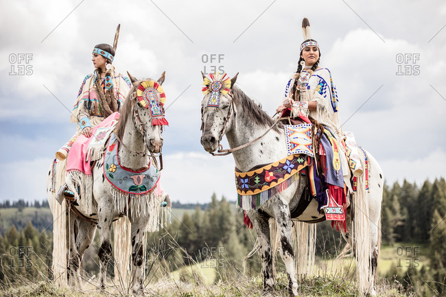 Two Native American sisters dressed in regalia riding horses on the Umatilla Reservation, Pendleton, Oregon