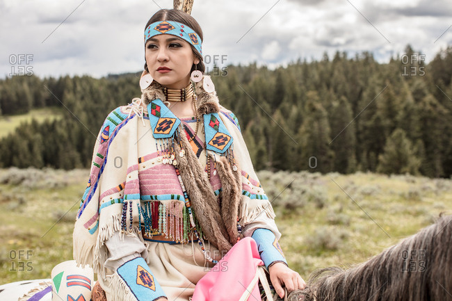 Girl dressed in Native American regalia riding a horse through the Umatilla Reservation, Pendleton, Oregon