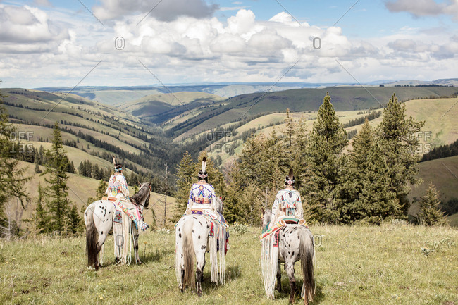 Rear view of Native American girls dressed in regalia riding horses on the Umatilla Reservation, Pendleton, Oregon