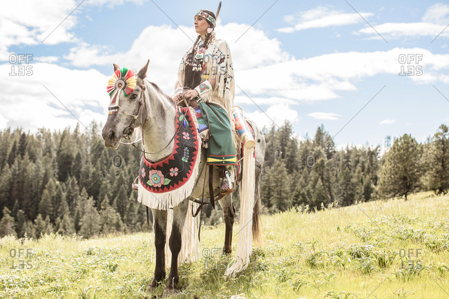 Young Native American woman in regalia riding a spotted horse on the Umatilla Reservation, Pendleton, Oregon