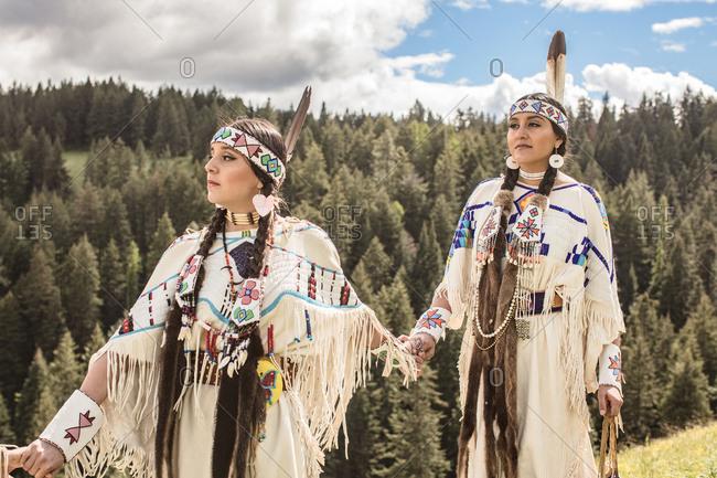 Sisters holding hands dressed in Native American regalia on the Umatilla Reservation, Pendleton, Oregon