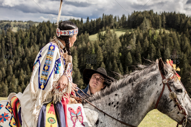 Native American young woman dressed in regalia riding horse beside a cowboy