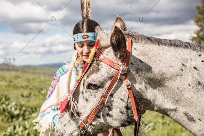 Native American girl in regalia with her horse on the Umatilla Reservation, Pendleton, Oregon