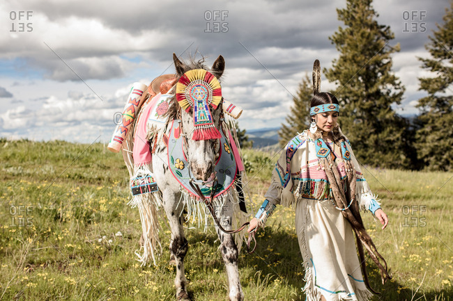 Native American girl in regalia walking with her horse on the Umatilla Reservation, Pendleton, Oregon