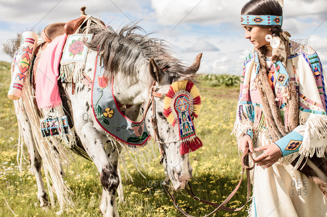 Native American girl in regalia with her horse grazing on the Umatilla Reservation, Pendleton, Oregon