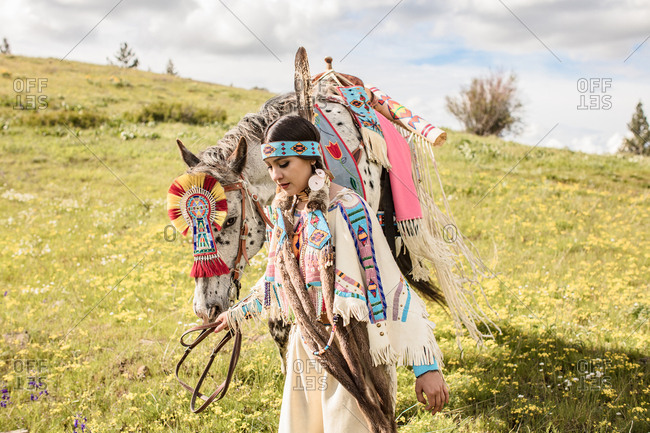 Young Native American woman in regalia walking with her horse on rolling hills