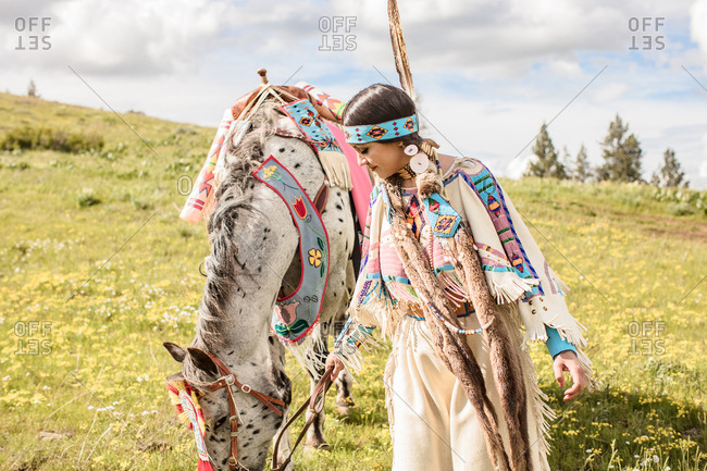 Young Native American woman in regalia with her horse grazing on rolling hills