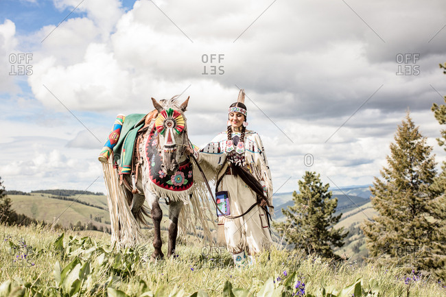 Young Native American woman wearing regalia with her horse on a hill