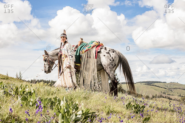 Young Native American woman in regalia with her horse on a hill