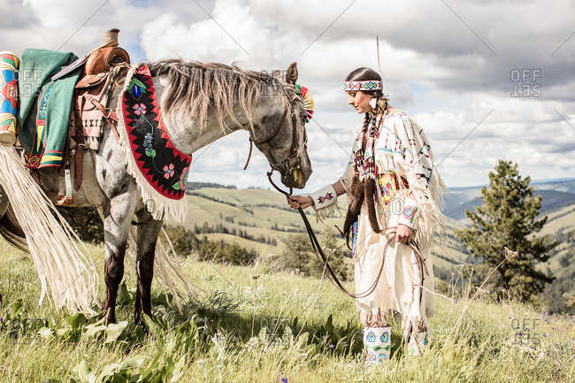 Native American girl in regalia with her horse grazing on a hill