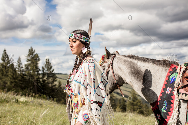 Native American girl in regalia walking with her horse on a hill