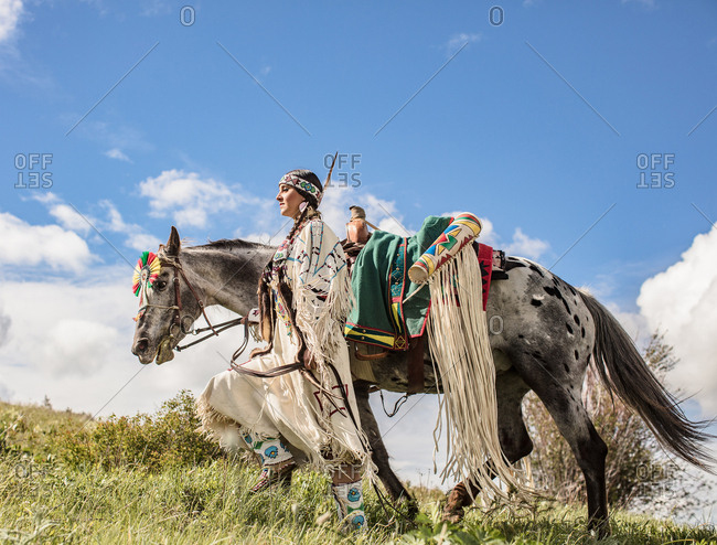 Native American girl wearing regalia walking with her horse on a hill