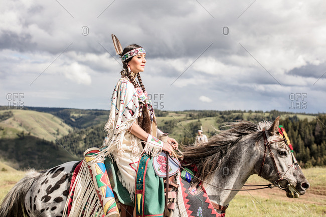 Young Native American woman wearing regalia riding her horse