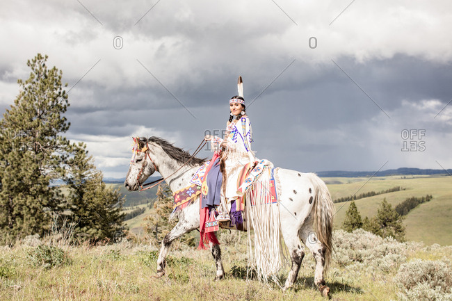 Young Native American woman wearing regalia riding her horse on a hill