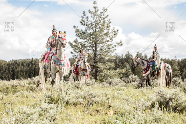 Three sisters riding horses in Native American regalia
