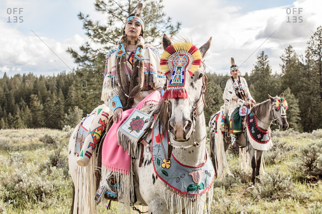 Two sisters riding horses in Native American regalia through the Umatilla Reservation, Pendleton, Oregon
