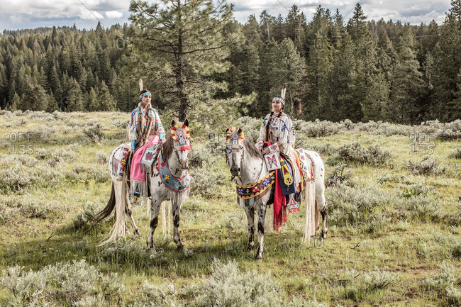 Two young women riding horses in Native American regalia on the Umatilla Reservation, Pendleton, Oregon