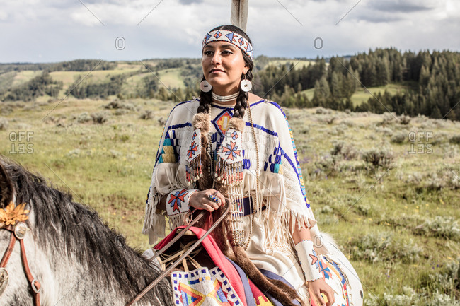 Young Native American woman wearing regalia riding her horse on the Umatilla Reservation, Pendleton, Oregon